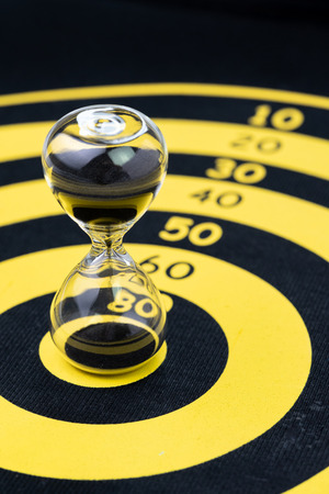 Deadline, time management or goal and target with time specific concept, hourglass or sandglass on yellow circle dartboard. Stock Photo
