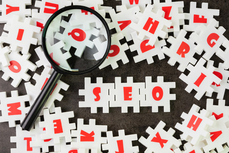 Search Engine Optimization, SEO concept, white puzzle jigsaw with alphabet building the word SEO at the center of dark chalkboard with magnifier glass