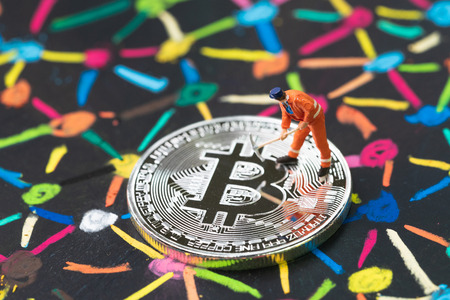 Bitcoin cryptocurrency concept, miniature worker digging or mining on physical shiny silver coin on colorful pastel chalk line link and connect between multiple dot or peer to peer on blackboard.