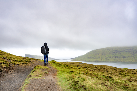 Young man walking or trekking on rural road beside the lake with bad weather raining in Faroe Islands, north atlantic ocean, Europe.