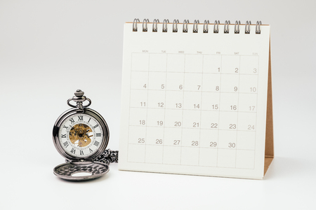 Vintage pocket watch with white clean desktop calendar on white background using as time passing, time management, year change or deadline concept.