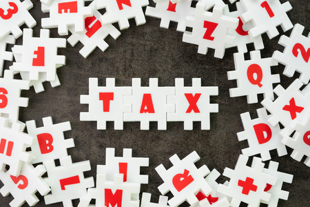 Tax concept, white puzzle jigsaw with alphabet building the word TAX at the center, yearly government pay back calculated from revenue.