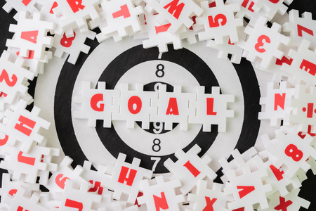 Business goal or target plan for success strategy concept, white puzzle jigsaw with alphabet word GOAL at the center on dartboard, measurable and realistic KPI to assess business performance.