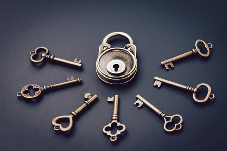 Security or secret protection concept, vintage brass padlock surrounded by multiple keys on a dark black background, internet hacker or cyber safety metaphor.