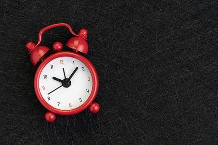 Self discipline, time, deadline and meeting schedule background with cute red alarm clock on dark black background with texture and copy space. Banco de Imagens