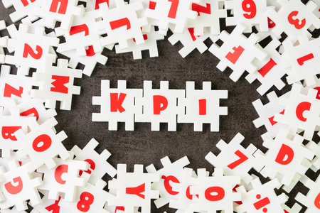 KPI, Key Point Indicator concept, white puzzle jigsaw alphabet combine word KPI at the center on dark black cement floor, business success target and measurement. Stock Photo