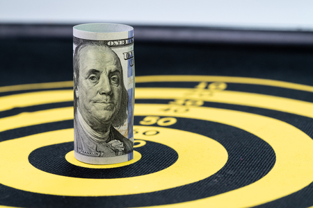 Financial goal or target concept, US Dollar banknote roll targeted at the center of yellow dartboard.