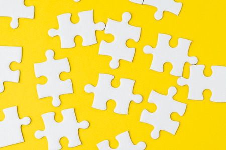 White jigsaw puzzle on solid yellow background metaphor solution to solving business problem, creativity, choice or teamwork concept.