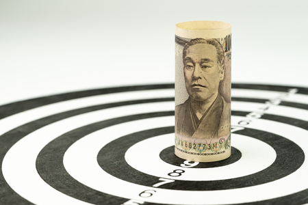 Financial goal or target concept, Japan Yen banknote roll targeted at the center of yellow dartboard.