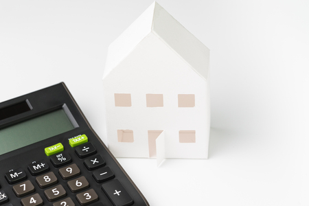 white paper house with black calculator on white background using as home loan, mortgate, rental cost and expense or investment in real estate concept.