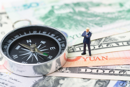 US and China finance economic direction, trade war, import and export deal and agreement concept, compass with miniature leader standing on US dollar and china yuan banknotes, tariff situation. Stock Photo