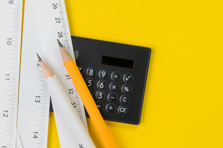 Calculator, pencils and white measuring tapes with centimetre and inches on vivid yellow background, length, long or maker instrument and enginerring tools concept.