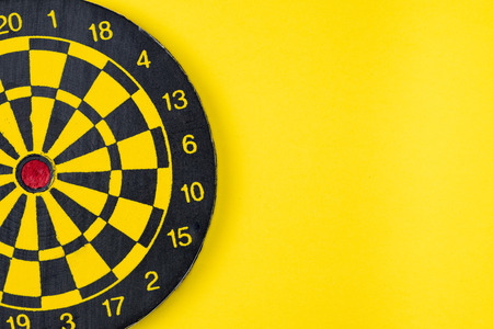 Flat lay of perfect black and yellow dartboard on solid yellow background with copy space using as business target and goals metaphor concept. Stock Photo