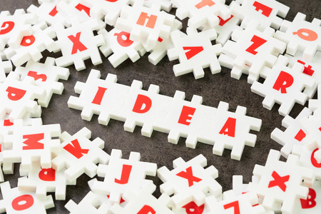 Idea, creativity or business solution concept, white puzzle jigsaw with alphabet building the word Idea at the center of dark chalkboard. Stock Photo
