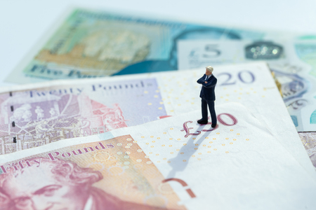 Miniature figure businessman leader standing and thinking on 5 pound sterling England currency banknotes, Brexit reconsider, UK economics, saving, financial or investment with Europe concept.