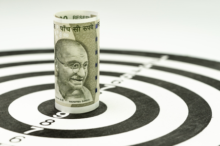 Financial goal or target concept, Indian rupee banknote roll targeted at the center of yellow dartboard.