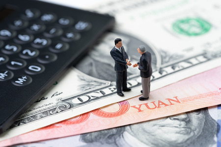 US and China finance economic direction, trade war, import and export deal and agreement concept, calculator with miniature leader hand shaking on US dollar and china yuan banknotes, tariff situation. Stock Photo