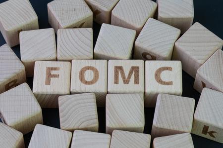 FOMC, concetto del Federal Open Market Committee, cubo di legno con alfabeto che costruisce la parola FED al centro su sfondo scuro della lavagna, l'istituzione per il controllo delle banche finanziarie statunitensi.
