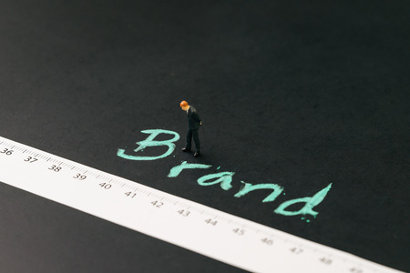Brand engagement KPI with measurable metrics in online and offline marketing campaign concept, miniature businessman standing with measuring tape with handwriting chalk word Brand on blackboard.