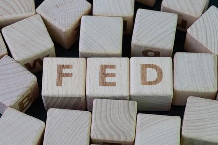 FED, concetto di Federal Reserve, blocco di legno cubo con alfabeto che costruisce la parola FED al centro su sfondo scuro lavagna, l'istituzione per il controllo delle banche finanziarie statunitensi. Archivio Fotografico
