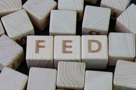 FED, Federal Reserve concept, cube wooden block with alphabet building the word FED at the center on dark blackboard background, the institution to control US financial banking.