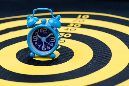 Deadline, time management or goal and target with time specific concept, retro blue alarm clock on yellow circle dartboard. Imagens