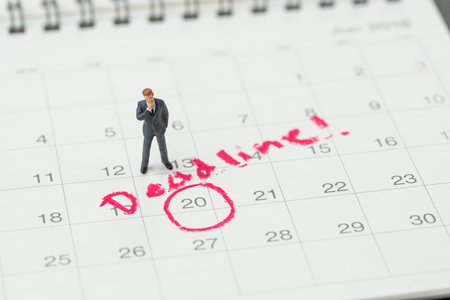 Miniature business man standing on desktop calendar with red circle on important date with handwriting deadline, goal or target date of work project plan, meeting or day of delivery. Imagens