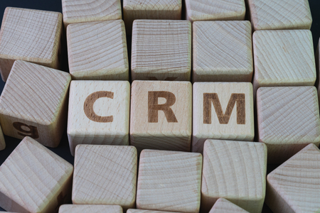 CRM, Customer Relationship Management, loyalty program, repeat purchase frequency concept, cube wooden block with alphabet combine the word abbreviation CRM on black background.