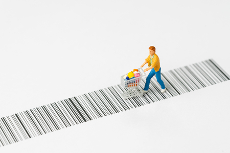 Miniature people figurine with grocery in the shopping cart or trolley rally on the bar code using as e-commerce with copy space, consumer or buy and sale in new technology channel concept. Banque d'images - 122490145