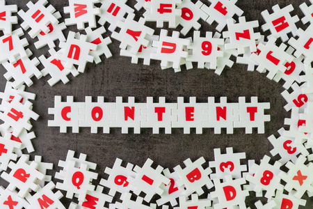 Content is king in advertising or creative communication concept, white puzzle jigsaw building the word content on dark black cement surrounded by other alphabets.