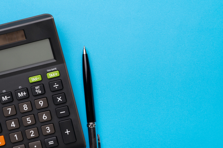 Financial activity, accounting, tax calculation or saving and investment, black calculator with pen on solid blue background with copy space.
