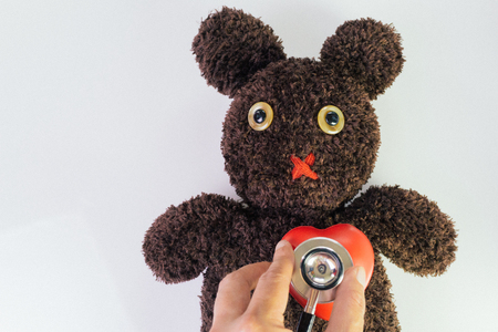 Doctor's hand holding stethoscope put on red heart on cute brown handmade fluffy doll with pitty eyes, healthcare for children or kids, medical learning class.