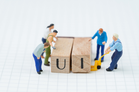 Building UI, User Interface concept, miniature people figure, workers, engineers building or moving wooden stamp block to arrange the abbreviation UI on grid line idea notebook.