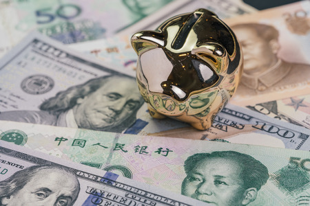 US and China Trade war and tariff negotiation concept, golden piggy bank on United States America and Chinese banknotes. Standard-Bild
