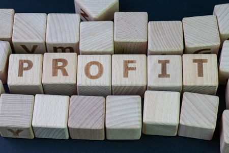 Profit in invesment, company revenue or financial income concept, cube wooden block with alphabet combine the word profit on black chalkboard background. 版權商用圖片