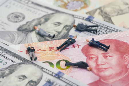 US and China Trade war and tariff negotiation fail concept, miniature figures businessmen leader falling apart on United States America and Chinese banknotes. Stock Photo