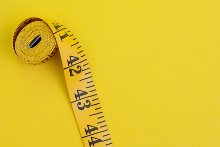 Yellow measuring tape on solid yellow background with copy space using as health fitness, nutrition, exercise or diet concept.