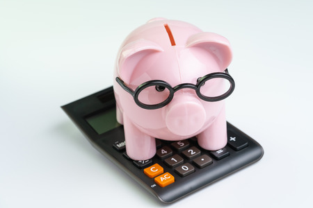 Pink piggy bank wearing glasses on black calculator on white background using as budget, cost or investment calculation and financial activity concept. Banco de Imagens