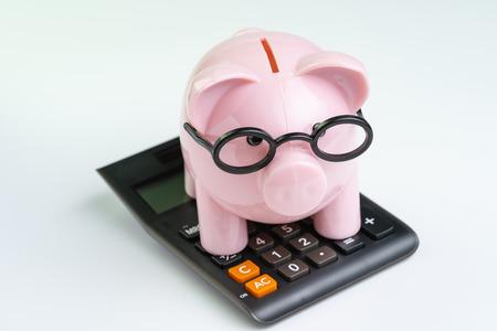 Tirelire rose portant des lunettes sur une calculatrice noire sur fond blanc utilisant comme budget, calcul de coût ou d'investissement et concept d'activité financière.