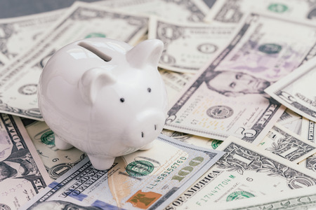 White piggy bank or coin bank on pile of US dollar banknotes money, investment growth, financial background or saving deposit concept.