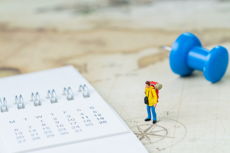 Travel, tourism, vacation or wanderlust life concept, miniature young man backpacker standing on vintage world map with compass, pushpin and calendar plan for next destination, new adventure journey.