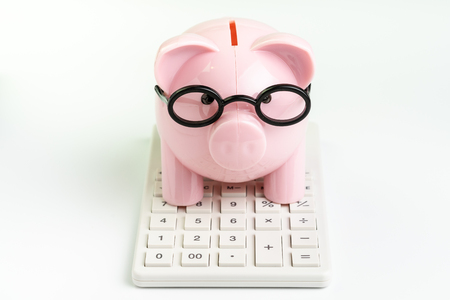 Budget, cost or investment calculation and financial activity concept, pink piggy bank wearing glasses on white calculator on white background.