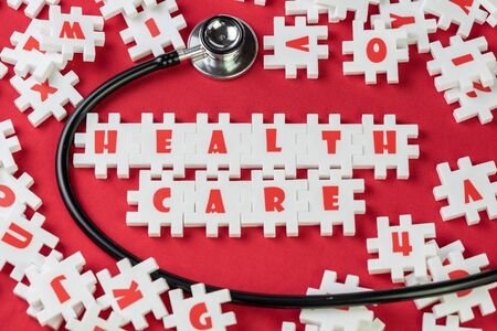 Health care concept, white jigsaw puzzle building the word Health care with stethoscope on red fabric background.