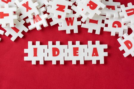 Business idea, creativity and imagination concept, abundance white puzzle jigsaw with alphabets combine word IDEA and other letter pieces pouring from glass bottle on red fabric background. Zdjęcie Seryjne