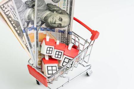Buy and sell house, property demand and supply or real estate purchasing concept, shopping cart or trolley with full of small cute miniature houses and US dollar banknotes money on white background.