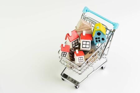 Buy and sell house, property demand and supply on real estate purchasing concept, shopping cart or trolley with full of small cute miniature houses on white background.