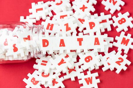 Big data analysis, unstructured database processing metaphor, large volume of  white puzzle jigsaws with alphabets pouring from bottle combine word DATA on red fabric background with copy space.