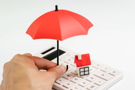 House maintenance and protection and home care service or cost calculation concept, human hand holding small umbrella over group of small miniature houses with red roof on white calculator. Stock Photo
