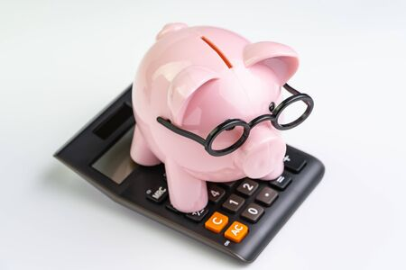 Pink piggy bank wearing glasses on black calculator on white background using as education budget, cost or investment calculation and financial activity concept. Reklamní fotografie - 124774948