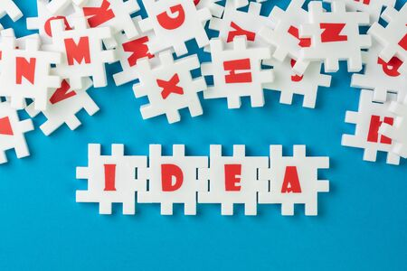 White puzzle jigsaws with alphabets building word IDEA at the center of other alphabets on blue background, business idea, creativity or inspiration in work and problem solving. Stock Photo